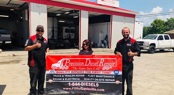 Staff Posing For Photo While Holding Precision Diesel Repair Banner