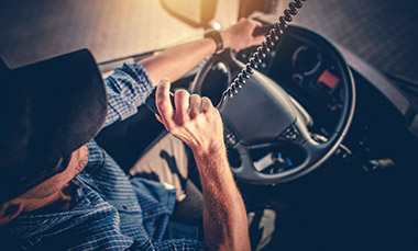Semi Truck Driver Making Conversation With Other Truck Drivers Through CB Radio